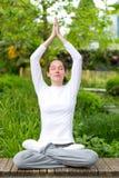 Yoga di pratica della giovane donna attraente in un parco Immagine Stock