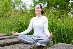 Yoga di pratica della giovane donna attraente in un parco Immagine Stock Libera da Diritti