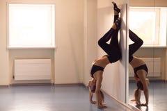 Yoga di pratica della giovane donna attraente vicino alla finestra Adho Mukha V Fotografia Stock Libera da Diritti