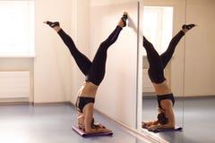 Yoga di pratica della giovane donna attraente vicino alla finestra Adho Mukha V Fotografie Stock Libere da Diritti