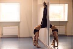 Yoga di pratica della giovane donna attraente vicino alla finestra Adho Mukha V Fotografia Stock