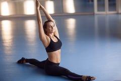 Yoga di pratica della giovane donna attraente vicino alla finestra Hanumanasana Immagine Stock Libera da Diritti
