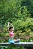 Yoga di pratica della giovane donna cinese esterna Fotografie Stock