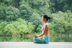 Yoga di pratica della giovane donna cinese esterna Immagine Stock