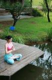 Yoga di pratica della giovane donna cinese esterna Fotografia Stock