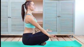 Yoga di pratica della giovane donna degli Yogi che si siede nella foto a figura intera di posa del loto di asana del namaste video d archivio