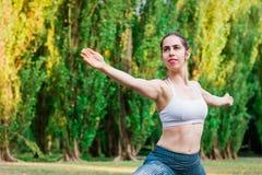 Yoga di pratica della giovane donna esile in natura Posa di Virabhadrasana immagini stock