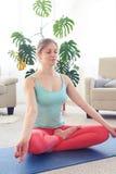 Yoga di pratica della giovane donna nella posa del loto dell'interno Fotografia Stock