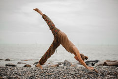 Yoga di pratica della giovane donna nella posa orientata verso il basso del cane sulla spiaggia Fotografie Stock