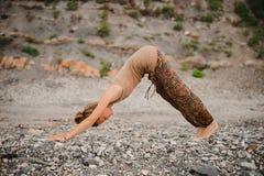 Yoga di pratica della giovane donna nella posa orientata verso il basso del cane sulla spiaggia Immagini Stock