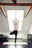 Yoga di pratica della giovane donna in salone Fotografie Stock Libere da Diritti