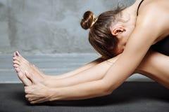 Yoga di pratica della giovane donna, sedentesi nell'esercizio di andata messo della curvatura, posa di paschimottanasana, risolve Fotografie Stock Libere da Diritti