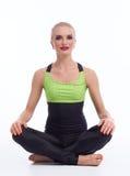 Yoga di pratica della giovane donna splendida che si siede sul pavimento Immagine Stock
