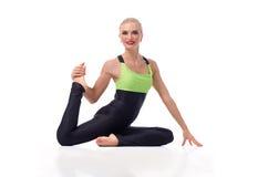 Yoga di pratica della giovane donna splendida che si siede sul pavimento Fotografia Stock