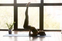 Yoga di pratica della giovane donna sportiva nella posa di Viparita Karani fotografie stock libere da diritti