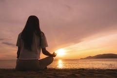 Yoga di pratica della giovane donna sulla spiaggia ad alba fotografia stock