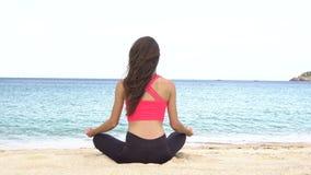 Yoga di pratica della giovane donna sulla spiaggia al tramonto Esercizi calma ed armonia Meditazione nella posa del loto Sano stock footage
