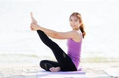 Yoga di pratica della giovane donna sulla spiaggia nell'allungamento della posa, wellnes Fotografie Stock Libere da Diritti