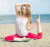 Yoga di pratica della giovane signora Allenamento vicino alla costa di mare dell'oceano Immagini Stock