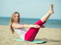 Yoga di pratica della giovane signora Allenamento vicino alla costa di mare dell'oceano Fotografie Stock