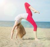 Yoga di pratica della giovane signora Allenamento vicino alla costa di mare dell'oceano Fotografie Stock Libere da Diritti