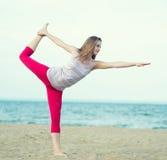 Yoga di pratica della giovane signora Allenamento vicino alla costa di mare dell'oceano Immagine Stock