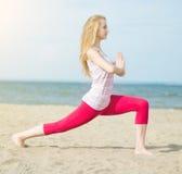 Yoga di pratica della giovane signora Allenamento vicino alla costa di mare dell'oceano Immagini Stock Libere da Diritti