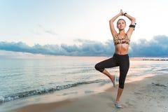 Yoga di pratica della ragazza adatta dei giovani sulla spiaggia ad alba Fotografia Stock Libera da Diritti