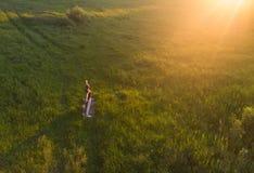 Yoga di pratica della ragazza al tramonto Immagini Stock