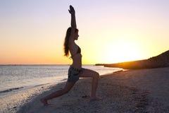 Yoga di pratica della ragazza contro il tramonto Fotografia Stock