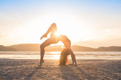 Yoga di pratica della ragazza sulla spiaggia al tramonto, bella spiaggia di meditazione di vacanze estive della donna immagini stock
