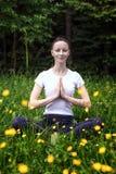 Yoga di pratica della ragazza in una foresta Immagine Stock