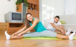 Yoga di pratica delle coppie a casa Immagine Stock