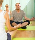 Yoga di pratica delle coppie mature con l'istruttore Immagine Stock