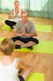 Yoga di pratica delle coppie mature con l'istruttore Fotografie Stock Libere da Diritti