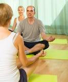 Yoga di pratica delle coppie mature con l'istruttore Immagine Stock Libera da Diritti