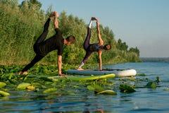 Yoga di pratica delle coppie sul fiume fotografia stock