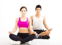 Yoga di pratica delle giovani coppie isolata su bianco Fotografia Stock