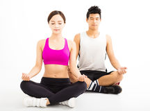 Yoga di pratica delle giovani coppie isolata su bianco Immagini Stock