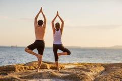 Yoga di pratica delle giovani coppie sulla spiaggia al tramonto Immagine Stock