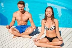 Yoga di pratica delle giovani coppie vicino alla piscina Fotografia Stock