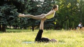 Yoga di pratica di acro delle belle coppie I giovani istruttori di yoga praticano in un parco della città su erba verde Due riusc video d archivio