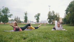 Yoga di pratica di tre giovane sportivi nel parco archivi video
