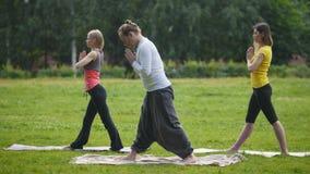 Yoga di pratica di tre giovane sportivi nel parco video d archivio