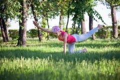Yoga di pratica e ginnastica della giovane donna flessibile nel parco Yoga nel parco, all'aperto, salute del ` s delle donne, don Fotografia Stock