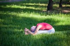 Yoga di pratica e ginnastica della giovane donna flessibile nel parco Yoga nel parco, all'aperto, salute del ` s delle donne, don Immagine Stock