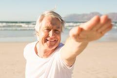 Yoga di pratica felice dell'uomo senior alla spiaggia Immagini Stock