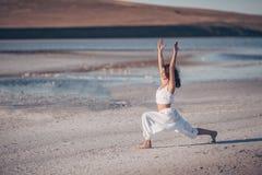 Yoga di pratica femminile attraente all'aperto Fotografia Stock