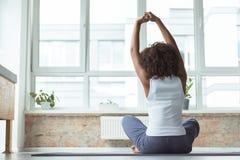 Yoga di pratica femminile sulla stuoia a casa Fotografia Stock Libera da Diritti