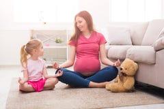 Yoga di pratica figlia della piccola e della madre a casa immagine stock